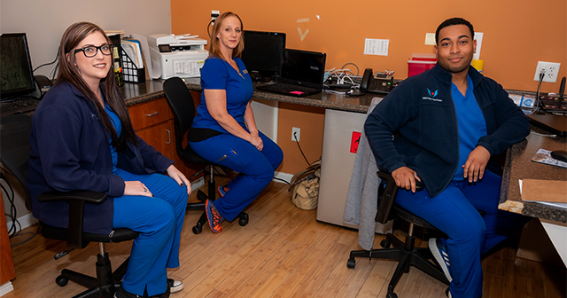 three specialist wearing blue medical uniform sitting in front of their desk