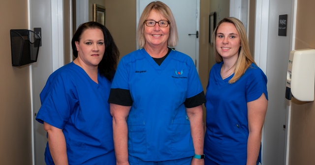 girls wearing blue medical uniform standing in the hall way